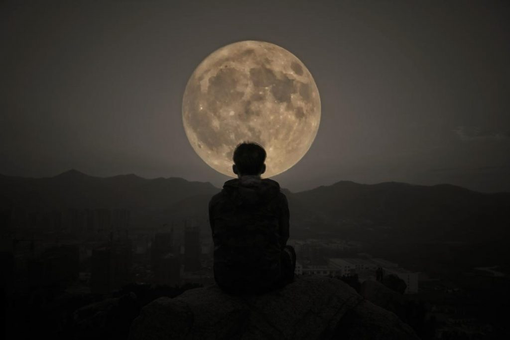 person looking at the full moon